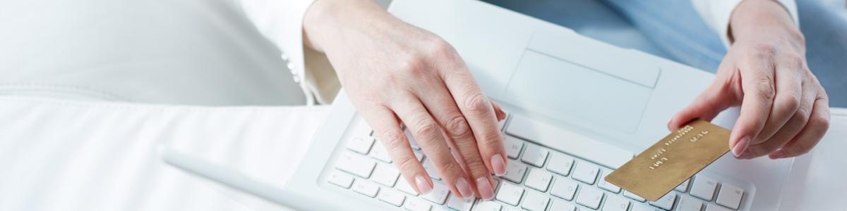hænder der holder et betalingskort over et tastatur