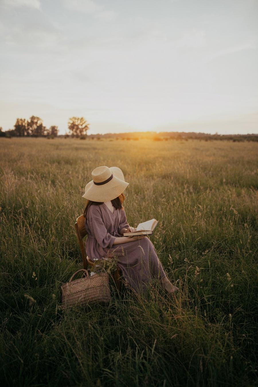 kvinde med stråhat læser bog
