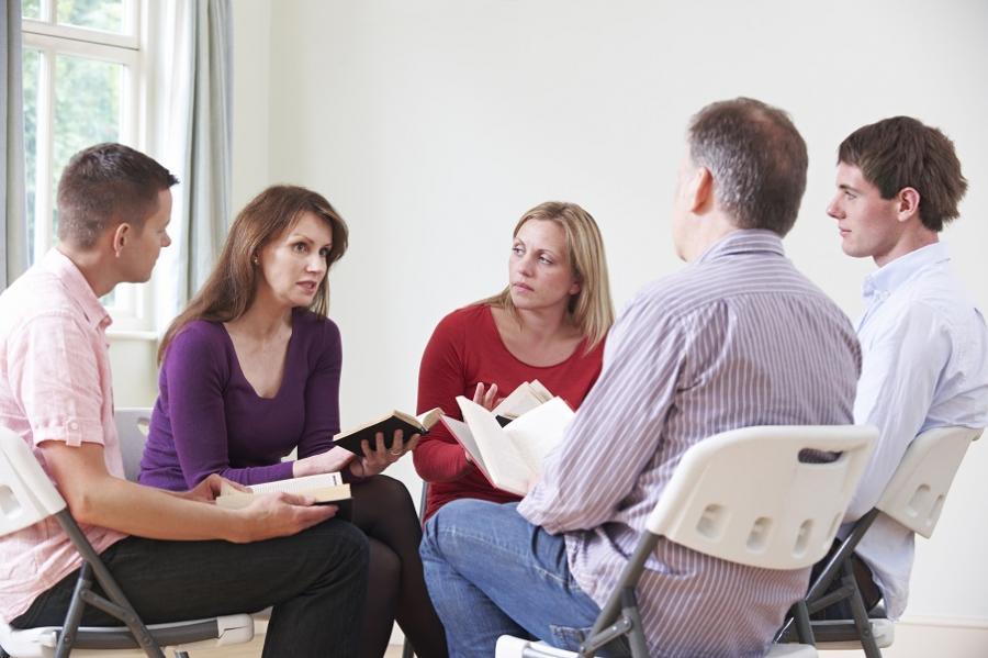 mænd og kvinder i en læsekreds snakker sammen